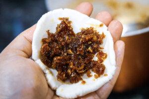 Filling the rice flour dough to make Kozhukatta Steamed Coconut Dumpling